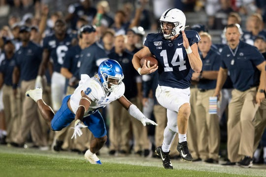 Penn State quarterback Sean Clifford (14) sprints away from Buffalo safety Joey Banks (9) on along gain during the third quarter of an NCAA college football game in State College, Pa., Saturday, Sept. 7, 2019.