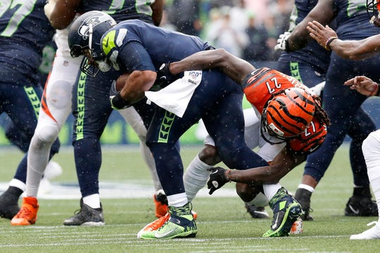 Cincinnati Bengals cornerback Dre Kirkpatrick (27) pulls down Seattle Seahawks quarterback Russell Wilson (3) for a sack in the third quarter of the NFL Week 1 game between the Seattle Seahawks and the Cincinnati Bengals at CenturyLink Field in Seattle on Sunday, Sept. 8, 2019. The Bengals lost 21-20 in the season opener.