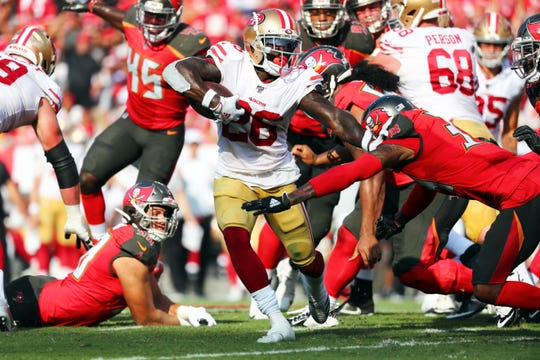 San Francisco 49ers running back Tevin Coleman (26) runs with the ball as Tampa Bay Buccaneers cornerback Carlton Davis (33) defends during the first half at Raymond James Stadium on Sept. 8.