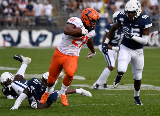 Illinois running back Ra'Von Bonner (21) breaks free of Connecticut linebacker D.J. Morgan (41) and runs in for a touchdown during the first half of an NCAA college football game, Saturday, Sept. 7, 2019, in East Hartford, Conn.
