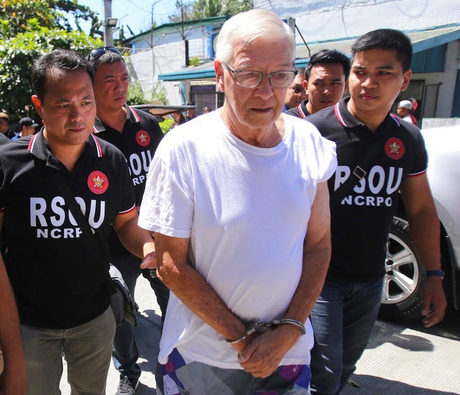 In this Feb. 19, 2019 photo, Philippine National Police, National Capital Region Police Office (NCRPO) agents escort Catholic priest Father Pius Hendricks to be served five additional arrest warrants at the Regional Special Operations Unit at Camp Bagong Diwa in suburban Taguig, east of Manila, Philippines. Investigators say about 20 boys and men, one as young as 7, have accused the priest of sexual abuse at his parish in Talustosan village, Naval township, Biliran province in central Philippines. (AP Photo)