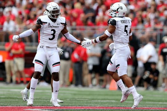 Cincinnati Bearcats safety Darrick Forrest (5) and Cincinnati Bearcats safety Ja'von Hicks (3) high five in the first quarter of a college football game against the Ohio State Buckeyes, Saturday, Sept. 7, 2019, at Ohio Stadium in Columbus.