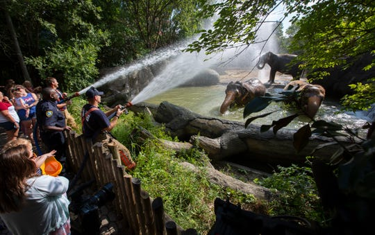 Firefighters from Cincinnati Fire Department Ladder Co. 32 give a firehose shower to the elephants in the Elephant Reserve at the Cincinnati Zoo and Botanical Garden, Monday, September 9, 2019. It was to kick-off Hometown Hero week at the zoo. Active fire and police personnel, as well as active and retired military will get in free to the zoo all week. At left on the firehose is firefighter Dennis Schwettmann, center firefighter Cornelius Lewis and at right, firefighter Ryan Pickering.