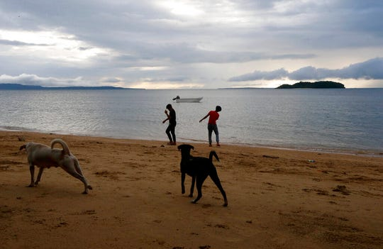 In this Jan. 27, 2019 photo, two boys play by the shore at a beach resort in Talustusan on Biliran Island in the central Philippines. Since December 2018, the small village has been rocked by controversy after about 20 boys and men, including these two, accused their Catholic parish priest Father Pius Hendricks of years of alleged sexual abuse. (AP Photo/Bullit Marquez)