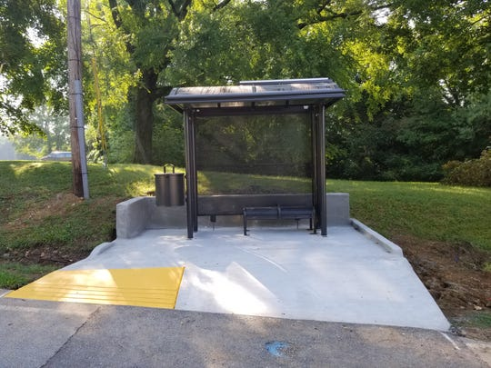 A city of Clarksville bus stop featuring solar-powered lighting, a bench, shade and trash can.