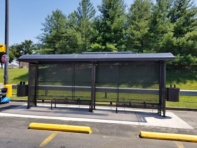 A city of Clarksville bus stop featuring solar-powered lighting, benches, shade and trash cans.