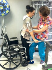 In this 2014 photo, Kaylee Hardenbrook works on physical therapy and tries to walk after an Eastern equine encephalitis infection left her paralyzed.