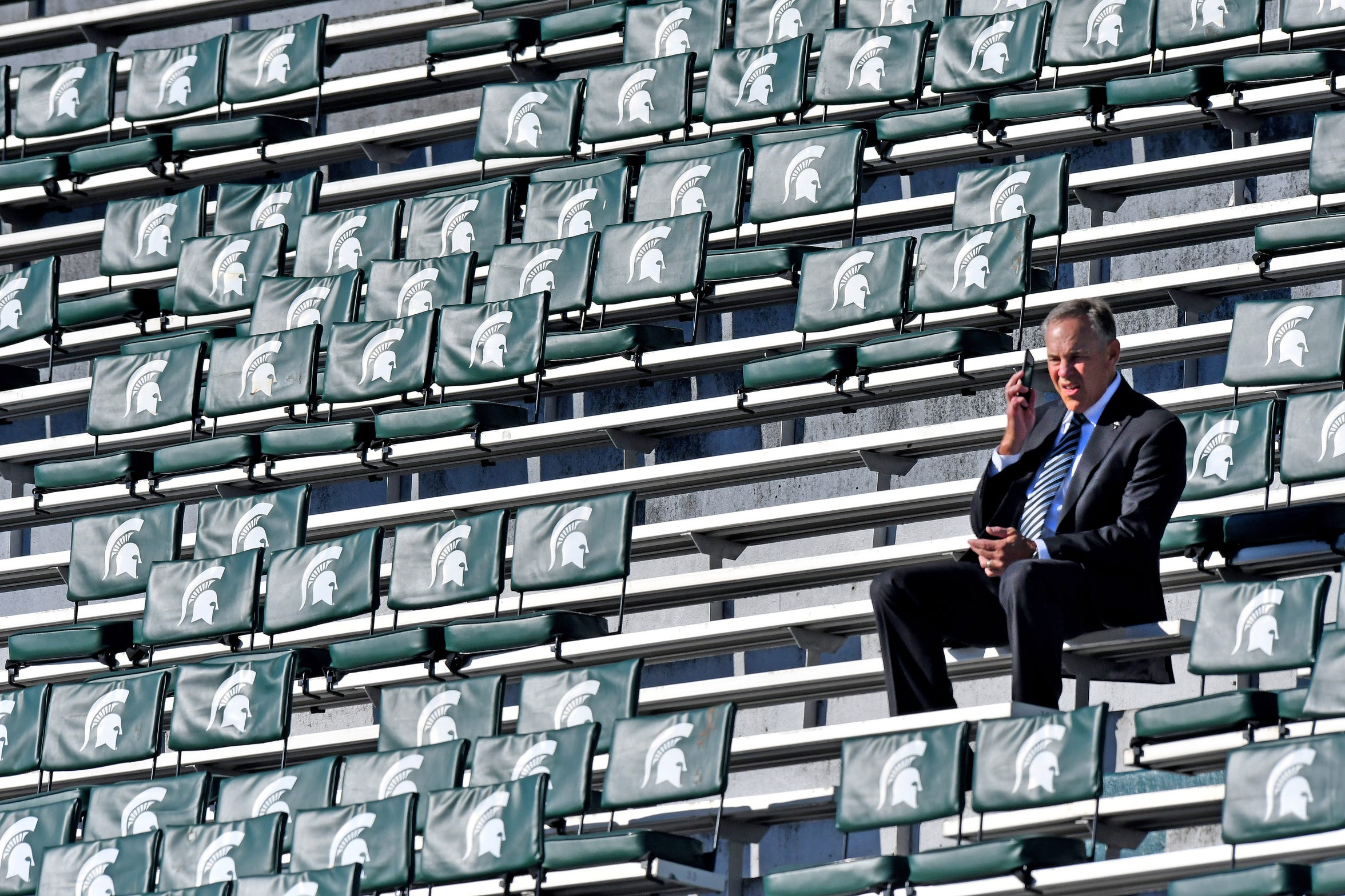 Head coach Mark Dantonio takes a phone call while sitting in the stands before Michigan State's 2018 game against Central Michigan.