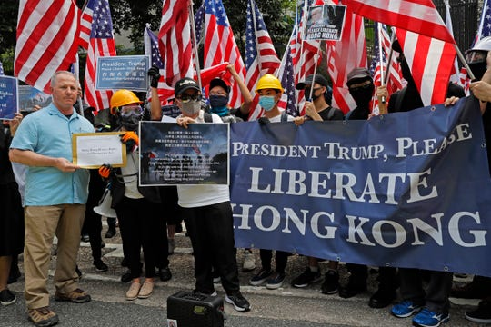 A U.S. Consulate representative, left, receives a letter from protesters as people march from Charter Garden to the US consulate in Hong Kong, Sunday