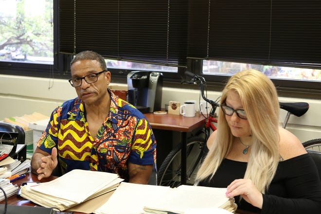 In this Tuesday, Sept. 3, 2019 photo, Hawaii Innocence Project co-director Kenneth Lawson, left, explains the case of a former U.S. soldier convicted of a 1982 murder, while University of Hawaii law student Alanna Wade looks through the legal file in Honolulu.