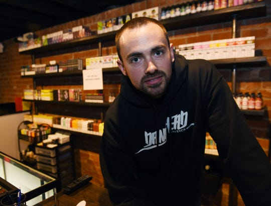 Nathan Esquivel, 27, owner of Corktown Smoke Shop, has marked down all of the shop's flavored e-cigarette liquids to move them out before the ban takes effect.