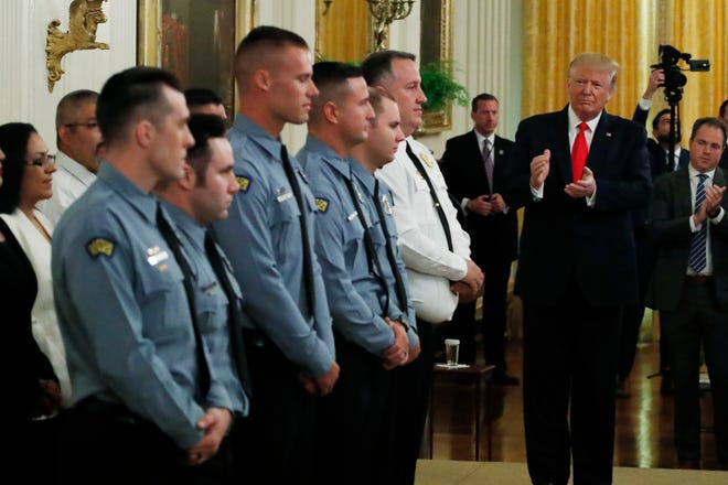 President Donald Trump applauds during a Medal of Valor and Heroic Commendations ceremony for six Dayton, Ohio police officers in the East Room of the White House, Monday, Sept. 9, 2019, in Washington, for stopping a mass shooter in August, in Dayton.