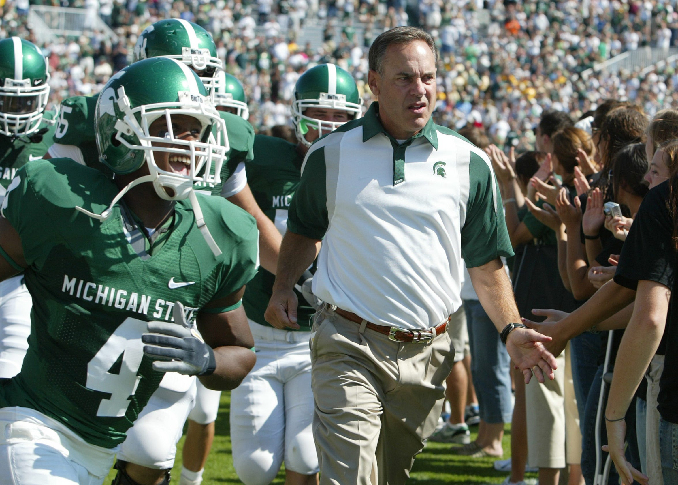 Mark Dantonio runs onto the field with his players before the start of his first game as coach, against UAB, Saturday, Sept. 1, 2007, in East Lansing.