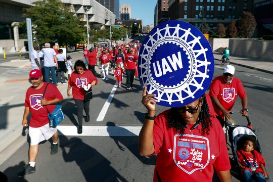 United Auto Workers members walk in the Labor Day parade in Detroit, Monday, Sept. 2, 2019.