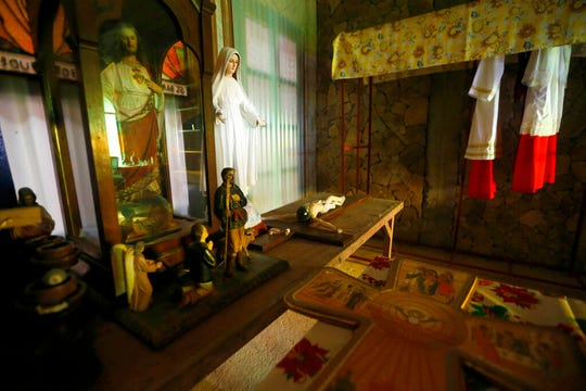 This Jan. 26, 2019 photo shows altar server vestments, right, and other religious images behind the altar chapel built by American priest Father Pius Hendricks in the village of Talustusan on Biliran Island in the central Philippines. Since December 2018, the small village has been rocked by controversy after about 20 boys and men accused the Catholic parish priest of years of alleged sexual abuse.