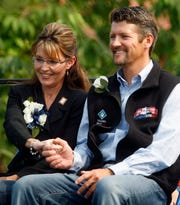 Former Alaska Gov. Sarah Palin holds her husband's Todd's hand as newly sworn in Gov. Sean Parnell gives his acceptance speech during a ceremony July 26, 2009, in Fairbanks, Alaska.