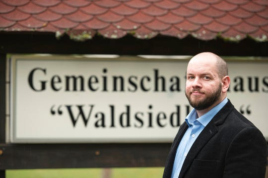 In this Sunday, Sept. 8, 2019 photo German far right party member Stefan Jagsch stands in front of the community house in the Altenstadt-Waldsiedlung, a part of the village of Altenstadt, near Frankfurt, Germany. Annegret Kramp-Karrenbauer, the leader of Merkel's Christian Democratic Union (CDU) said late Sunday the election of far-right NPD party member Jagsch needs to be reversed.
