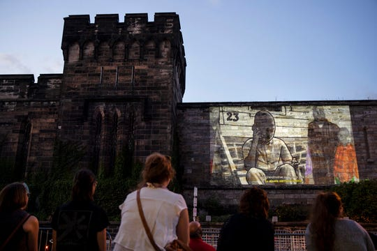 """In this Tuesday, Sept. 3, 2019 photo, people view incarcerated filmmaker Robert's animated short titled """"A Special Person"""" projected on the wall of Eastern State Penitentiary in Philadelphia. The former prison-turned-museum is showcasing animated short films by currently incarcerated inmates in a new exhibit titled """"Hidden Lives Illuminated."""""""