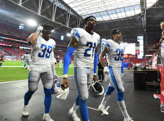 Lions Jamal Agnew, Tracy Walker and Mike Ford leave the field after Sunday's 27-27 tie with the Cardinals.