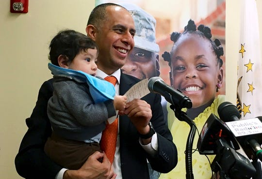 In this March 20, 2019, photo, Mayor Jorge Elorza holds his son Omar during a news conference in Providence, R.I.