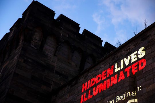 """In this Tuesday, Sept. 3, 2019 photo a new exhibit titled """"Hidden Lives Illuminated"""" is projected on a wall of the Eastern State Penitentiary, a former prison that's now a museum."""