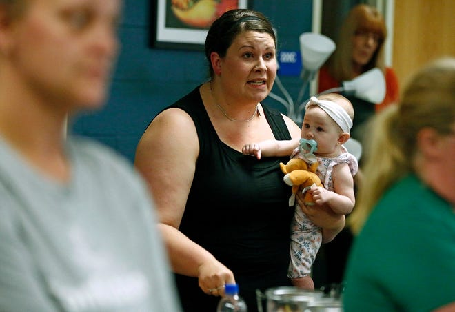 In this Aug. 22, 2019 photo, Jessica Moloney, holding her 6-month-old daughter Amelia, expresses her displeasure at a meeting at Highland High School in Marengo, Ohio, about how the school board handled a recent incident where a child had access to a gun, pointed it at another student, and that parents weren't informed.