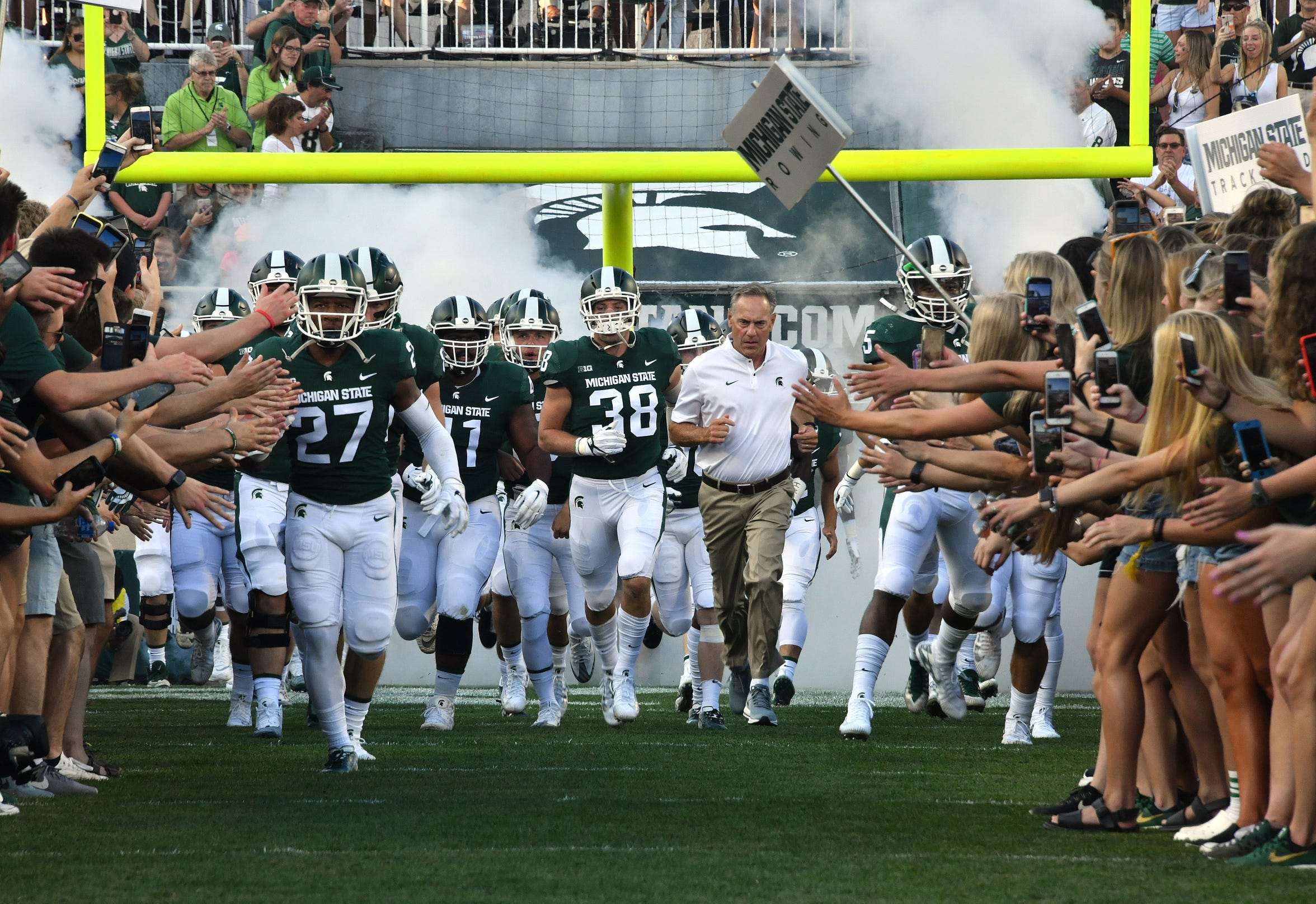 Mark Dantonio and his team run onto the field before Michigan State plays Utah State in 2018.