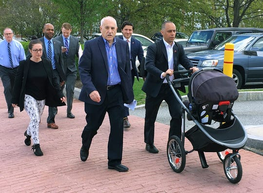 In this May 8, 2019 photo, Providence Mayor Jorge Elorza, right, pushes his son Omar in a baby carriage as he walks to the Rhode Island Statehouse for a meeting with the governor in Providence, R.I.