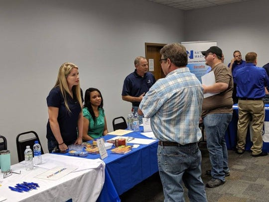 Employers from Sandusky and Seneca counties meet with Atlas Industries employees who were let go after the company announced its closure on Friday.