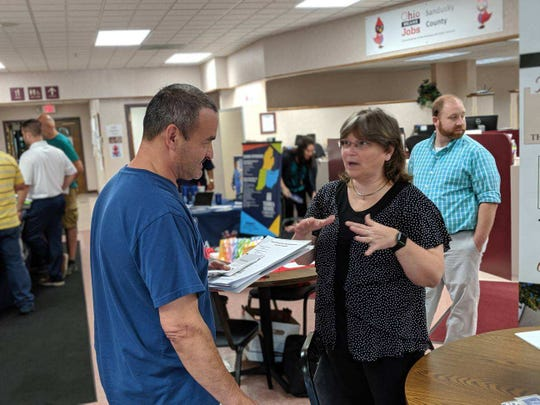 Dan Gonzales talks to Patricia Gerber, a retirement planner from Ashley Retirement Services, during Monday's job fair for former employees of Atlas Industries.