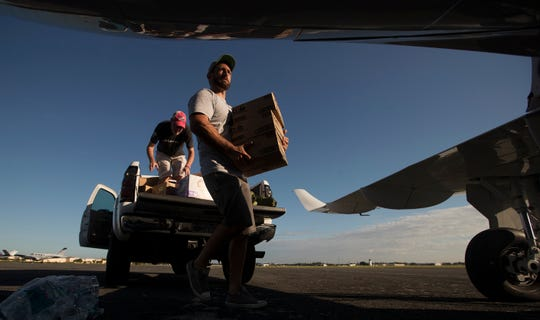 Kellen Luksch, center, helps load supplies on Monday for a Hurricane Dorian relief mission from Page Field Airport in Fort Myers to the Bahamas. Three planes carried more than 3900 pounds of supplies that were donated by the Southwest Florida community.