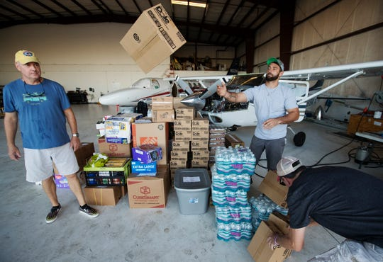 Glenn Frith, left, and Kellen Luksch, center, of Aeronautical Charters, Inc., help load supplies on Monday for a Hurricane Dorian relief mission from Page Field Airport in Fort Myers to the Bahamas. Three planes carried more than 3900 pounds of supplies that were donated by the Southwest Florida community.