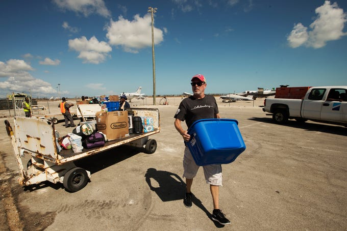 Will Prather takes food to people outside the gates of the Grand Bahama International Airport in Freeport, Bahamas on Monday. The effort was part of a Hurricane Dorian relief mission from Fort Myers to the Bahamas. Three planes carried more than 3900 pounds of supplies that were donated by the Southwest Florida community.