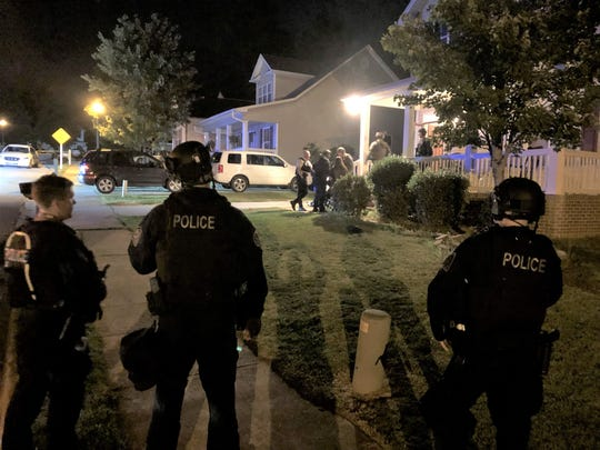Greenville police stand outside a home during a standoff.