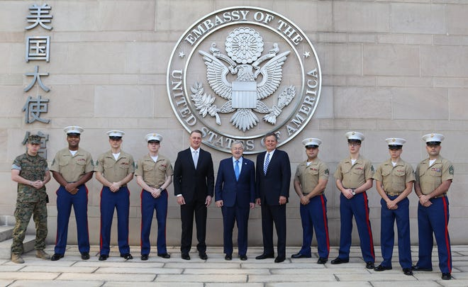 U.S. Marines stand with Sen. David Perdue , left, U.S. Ambassador to China Terry Branstad, center, and Sen. Steve Daines at the U.S. Embassy in Beijing.