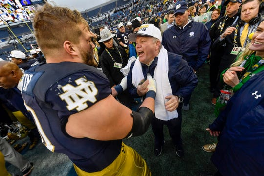 Notre Dame Fighting Irish head coach Brian Kelly gets a congratulation from Notre Dame Fighting Irish offensive lineman Hunter Bivin (70) at midfield after their Citrus Bowl victory against the LSU Tigers on January 01, 2018, at Camping World Stadium in Orlando, FL. Notre Dame defeated LSU 21-17.