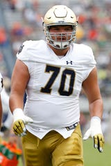 Fighting Irish offensive lineman Hunter Bivin (70) participates in warm-ups prior to the Fighting Irish' game against the Virginia Cavaliers at Scott Stadium.