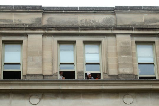 University of Iowa students peer out of a window to watch Democratic presidential candidate U.S. Sen. Bernie Sanders, I-Vt., speak to supporters, Sunday, Sept. 8, 2019, on the Pentacrest in front of the Old Capitol Building on the University of Iowa campus in Iowa City, Iowa.