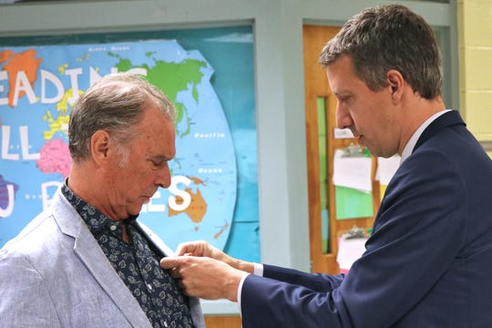 Vincent Sciama, Consul General of France in Louisiana, pins a purple medal to Francophone singer-songwriter Zachary Richard, promoting Richard to officer in the French Academic Palms Monday, Sept.9, 2019
