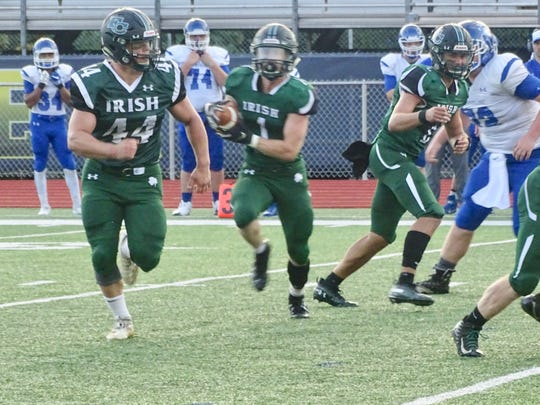 Fisher Catholic's Trey Fabricini blocks for Caden McColley during the Irish's 55-14 win over Crestline. Mccolley had a rushing touchdown and caught a touchdown pass.