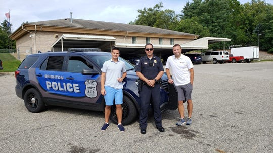 High school student Adrian Kozakov (left), Brighton Police Deputy Chief Craig Flood and Fund A Life founder Mark Howell stand by a police cruiser in Brighton. Kozakov is organizing a charity car rally to raise funds for Fund A Life.