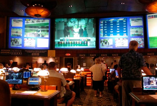 In this June 14, 2018 photo, bettors wait to make wagers on sporting events at the Borgata casino in Atlantic City, N.J., hours after it began accepting sports bets. The Borgata announced, Wednesday, Jan. 9, 2019, it will begin an $11 million expansion of its sports betting facility, to be completed by summer. (AP Photo/Wayne Parry)