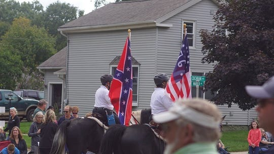 A woman carries the Confederate battle flag at the Charlotte Frontier Days festival on Sept. 7, 2019.