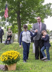 Benjamin Hall with sons Wells, 9, left, and JohnHenry, 7, right,  at marker of Merry Willis at Maple Grove Cemetery in Mason, Sunday, Sept. 8, 2019.