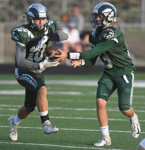 Madison quarterback Kaden Mullins hands the ball off to Jarrett Mandusic in Week 1 against Shelby.