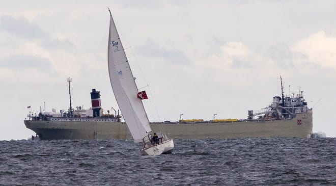 A sailboat cruises while the bulk carrier SS Alpena passes in the background Sunday, Sept. 8, 2019, on Green Bay west of Sturgeon Bay, Wis.