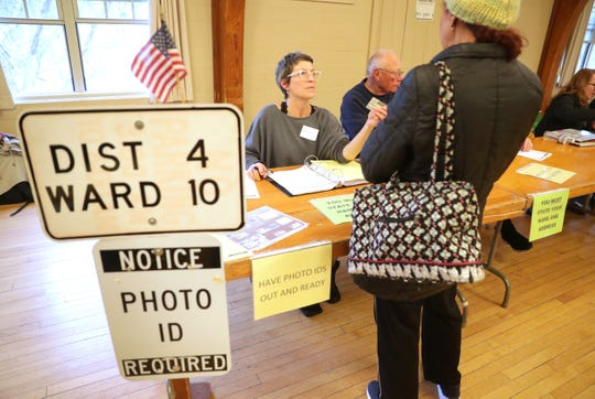 Poll worker Dawn-Marie Metz checks a voter's identification at the Hart Park Senior Center in Wauwatosa, on Tuesday, Nov. 6, 2018.