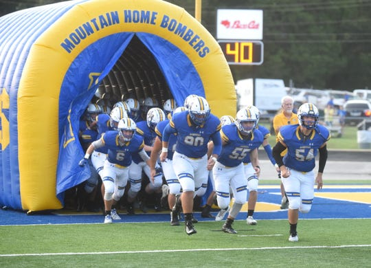 Mountain Home Bomber football players run onto the field before their game against Harrison.