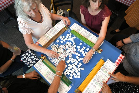 Michelle Tishler, top right, leads a game of mahjong with friends at Corner Pub in the Woods in Bellevue on Sept. 4, 2019.  Tishler, who learned mahjong from the women in her family, also teaches the game.