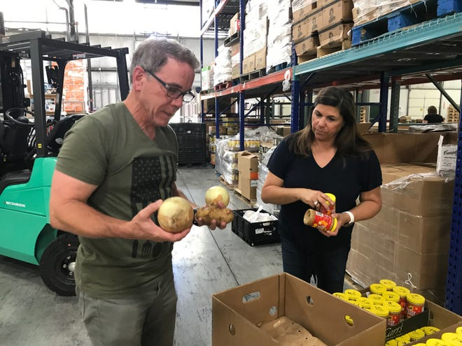 Co-founders of the Franklin One Gen Away food distribution nonprofit, Chris and Elaine Whitney, prepare food boxes for transport to Florida this week to provide disaster relief assistance. The main items people want are peanut butter, potatoes and onions, the Whitneys said.